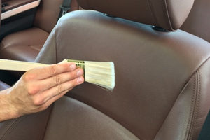 Close up of hand using a brush to clean and remove dust or dirt on the car seat